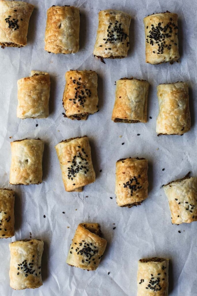An overhead geometric image of lines of freshly baked no-sausage rolls on textured baking paper. The lines are more scattered towards the bottom of the tray.