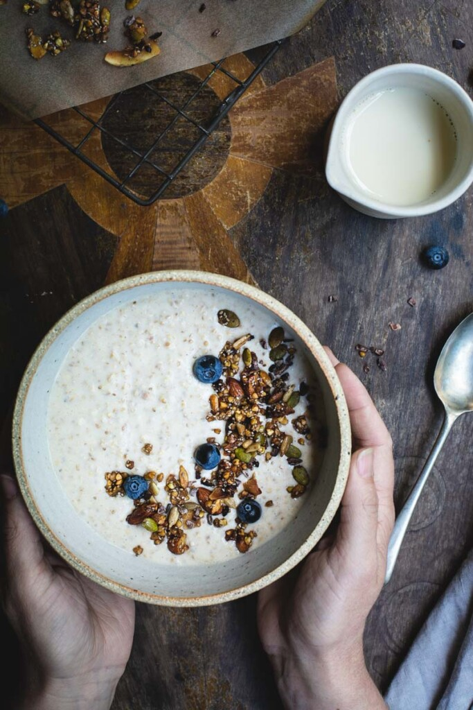 An overhead image of a rustic wooden table with a woman's hands holding a bowl of peanut butter overnight oats sprinkled with granola and blueberries. A tray of freshly baked granola is peaking in from the top left corner and a jug of almond milk sits off to the top right.