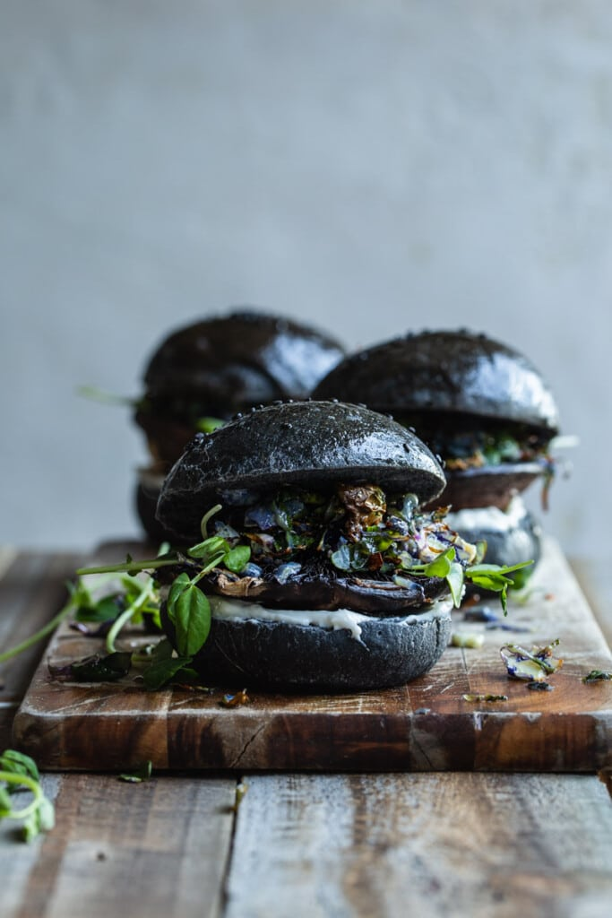 A front on image of 3 portobello mushroom burgers in charcoal buns sitting on a rustic wooden board. The front centre burger is in focus.