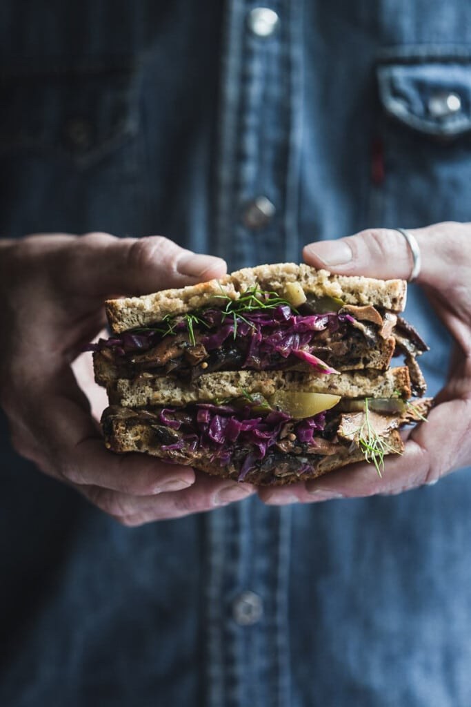 A picture of a man wearing a denim shirt. The image is cropped to his mid-section and is focusing on his hands holding a vegan mushroom sandwich.
