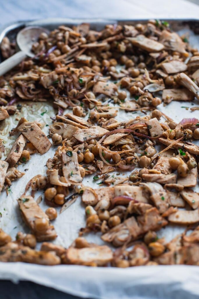 A close-up image of a tray of freshly roasted vegan shawarma with jackfruit and chickpeas on a lined roasting tray. A wooden spoon sits on the tray angled to the left.