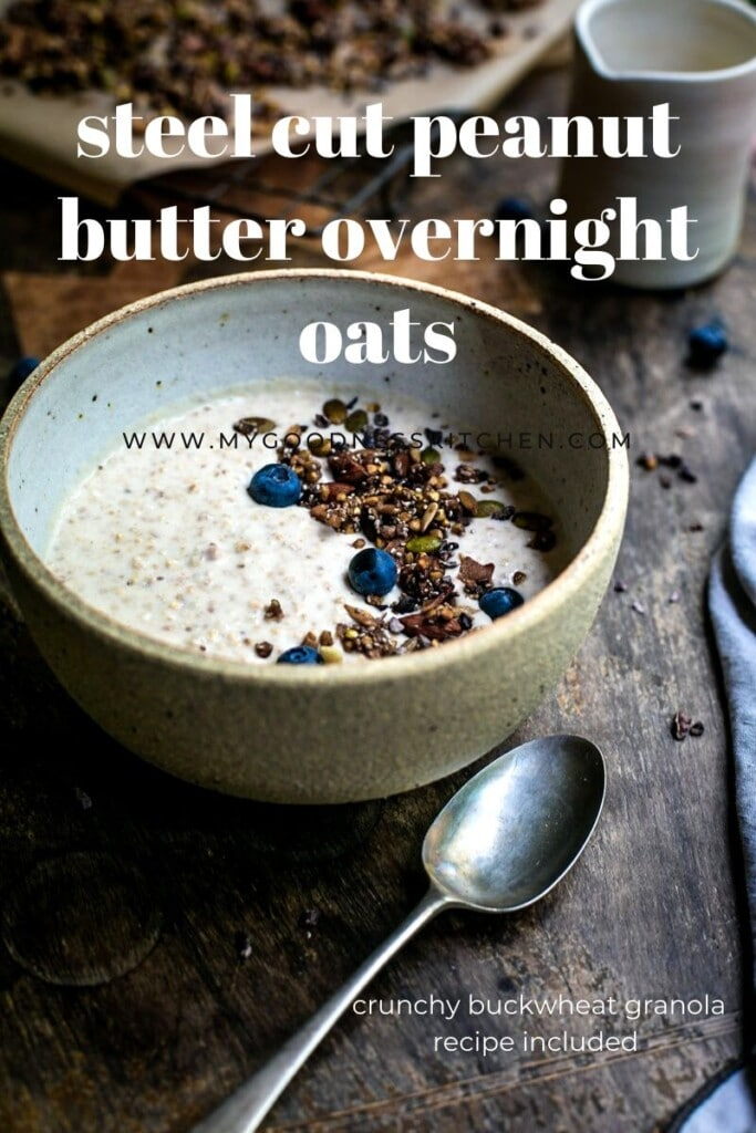 A bowl of overnight oats with granola sits on a rustic wooden table with a spoon and textured blue napkin nearby.