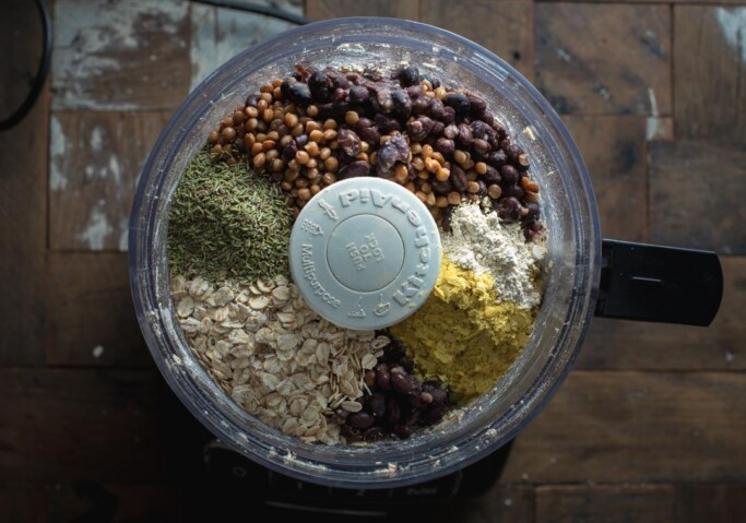 Overhead image of a food processor with the ingredients for BBQ vegan black bean burgers inside with the beans and lentils on top.