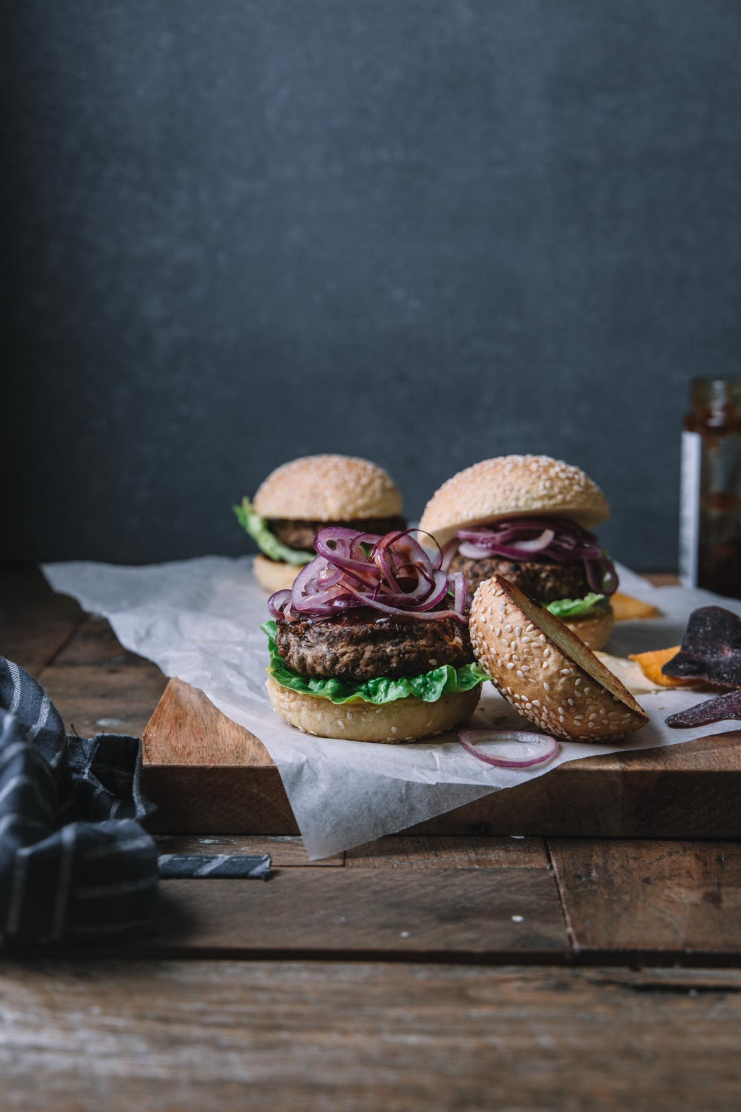 Black bean burgers in buns sitting on a wooden block