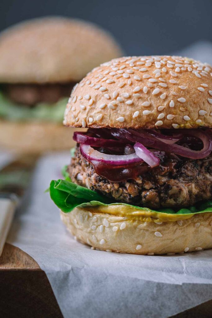 Close-up front image of a BBQ vegan black bean burger sitting on a wooden board set off-centre of the frame so we see three-quarters of the burger super close up. The burger has mustard, lettuce, a Pattie, BBQ sauce and fried red onion on a seeded bun.