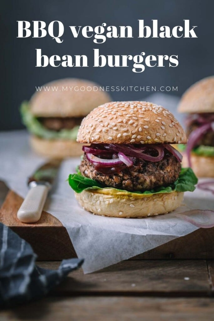 Front on image of a BBQ Vegan Black Bean Burger sitting on a rustic wooden board with two burgers in the background. Title text overlay in white.