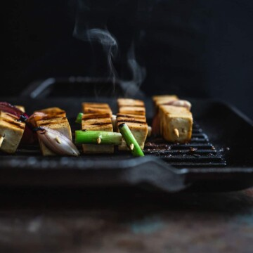 Tofu on skewers cooking on a hot grill