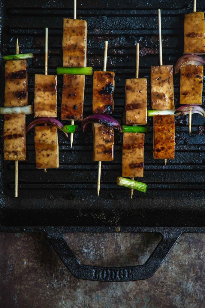 An overhead shot of the tofu yakitori skewers grilling on the Lodge Grill pan with deep grill marks on the tofu