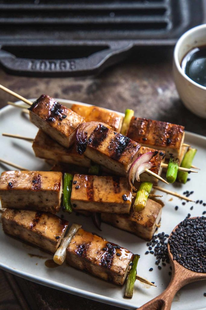 A close up image of a heaped pile of grilled tofu yakitori skewers sitting on a rectangle white serving plate. The cooking glaze shines on each skewer.