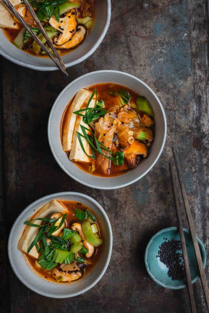 Kimchi stew in white bowls on a rusted background