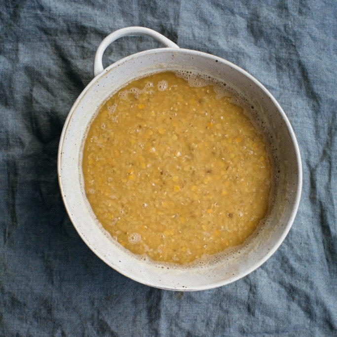 A bowl of soaking lentils on a cloth