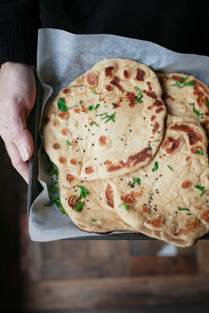 A close up of a person holding a tray of naan breads