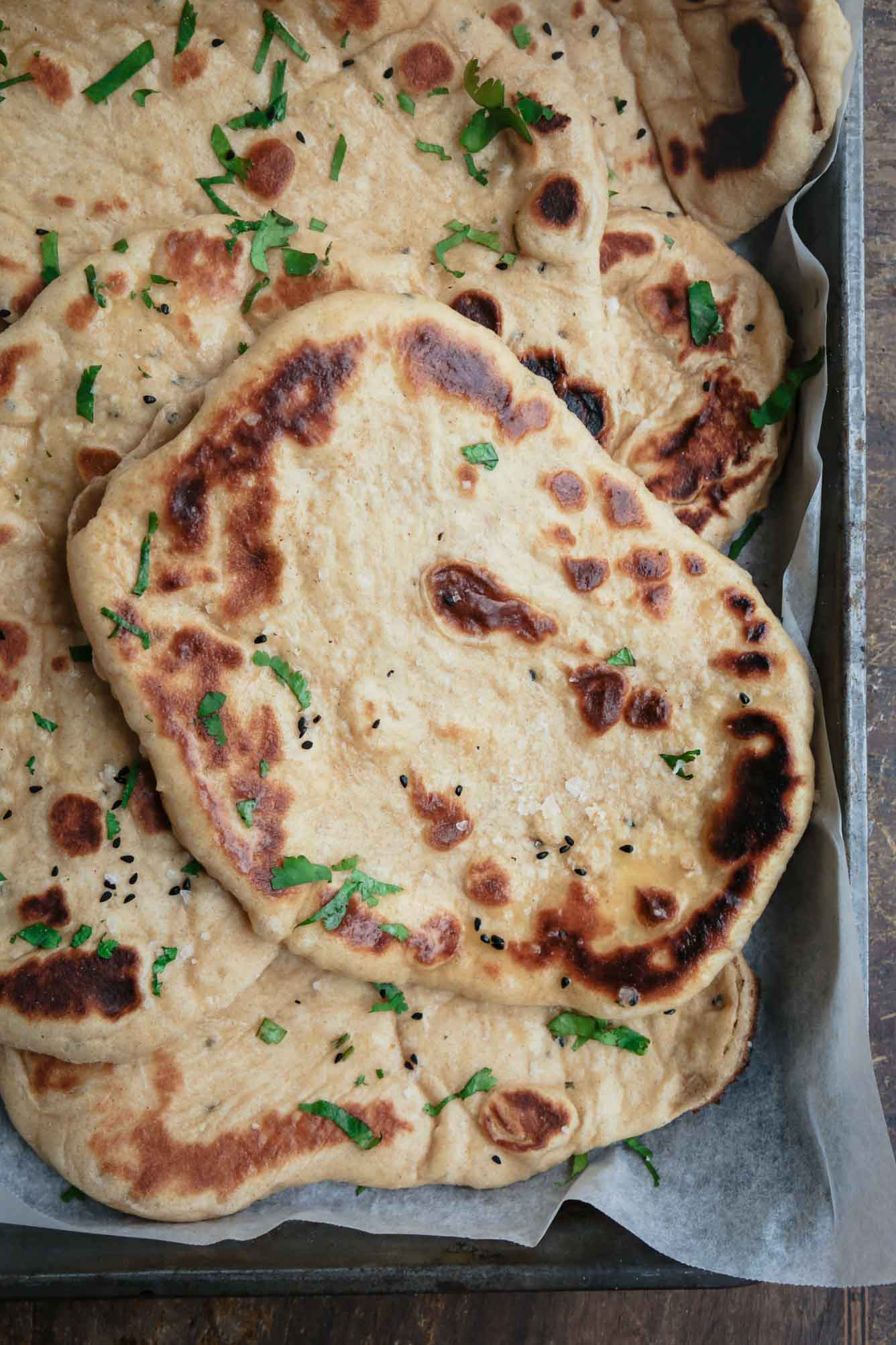 Overhead image of a freshly grilled pile of pillowy homemade vegan naan.