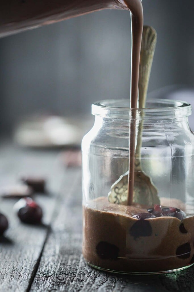 A chocolate drink being poured over cherries in a jar.