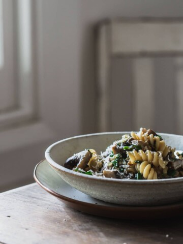 A white bowl of mushroom pasta sitting on a wooden table.