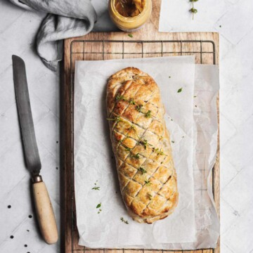 An uncut pastry roll on a cutting board on a table setting.