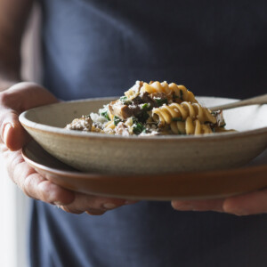 Man holding a bowl of mushroom pasta.