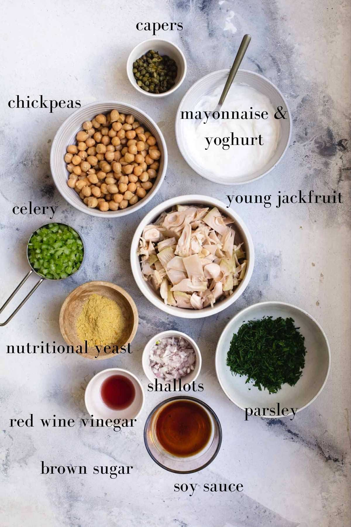 Ingredients for a vegan chicken salad in bowls on a marble background with labels.