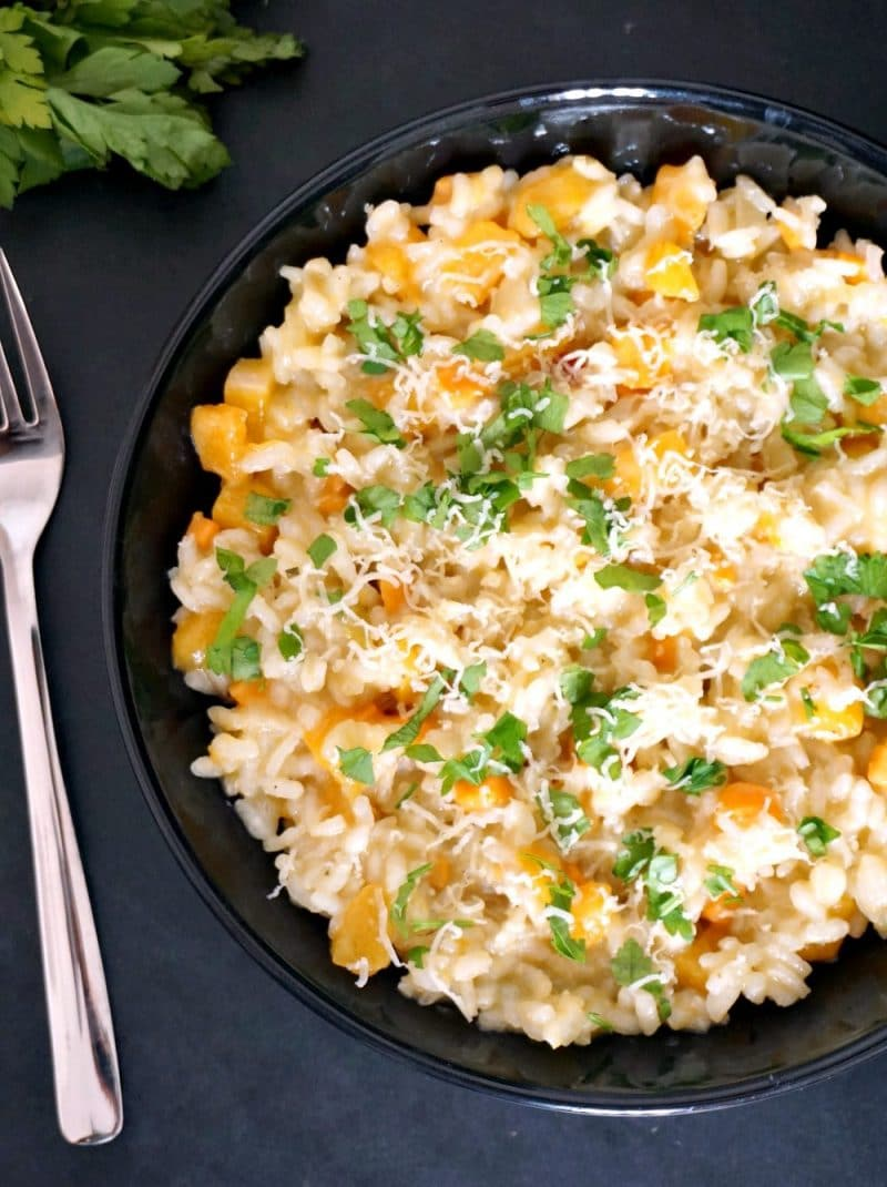 Overhead shoot of a black plate with butternut squash risotto