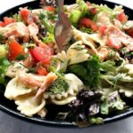 A black bowl of pasta salad with salmon and vegetables