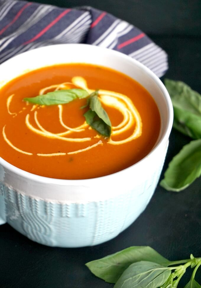 A bowl of Roasted Tomato and Red Pepper Soup garnished with cream and basil