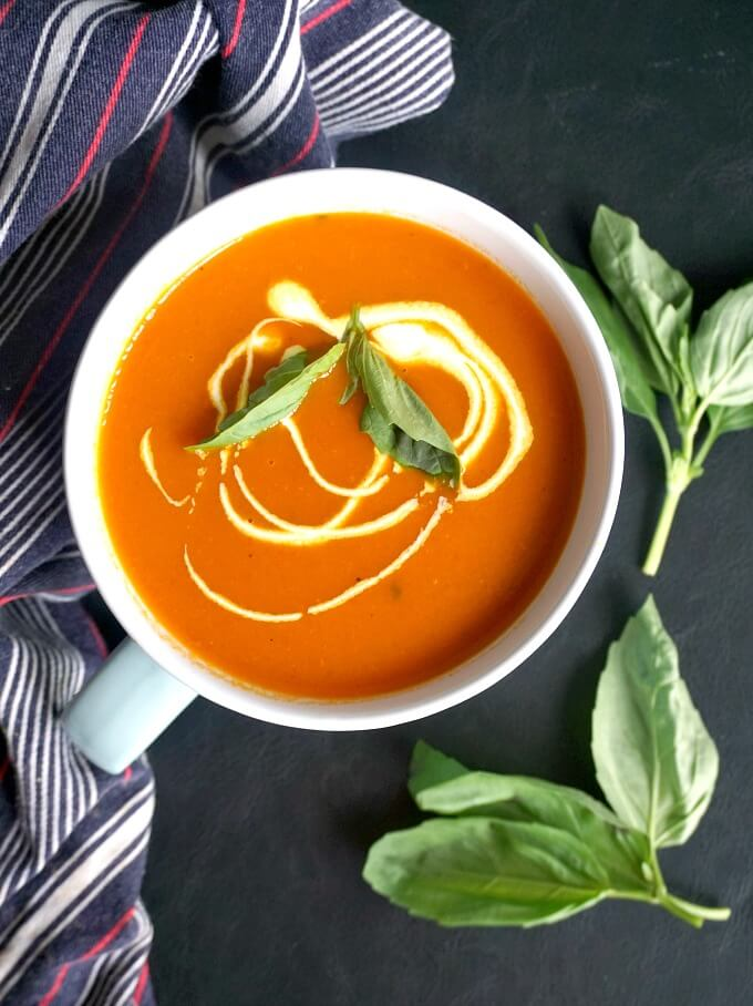Overhead shot of a bowl of Light Roasted Tomato and Red Pepper Soup garnished with basil leaves