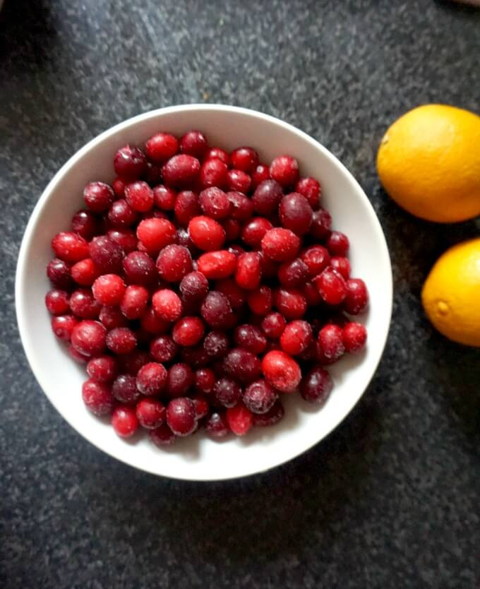 Overhead shot of a white bowl of frozen cranberries with 2 oranges next to it