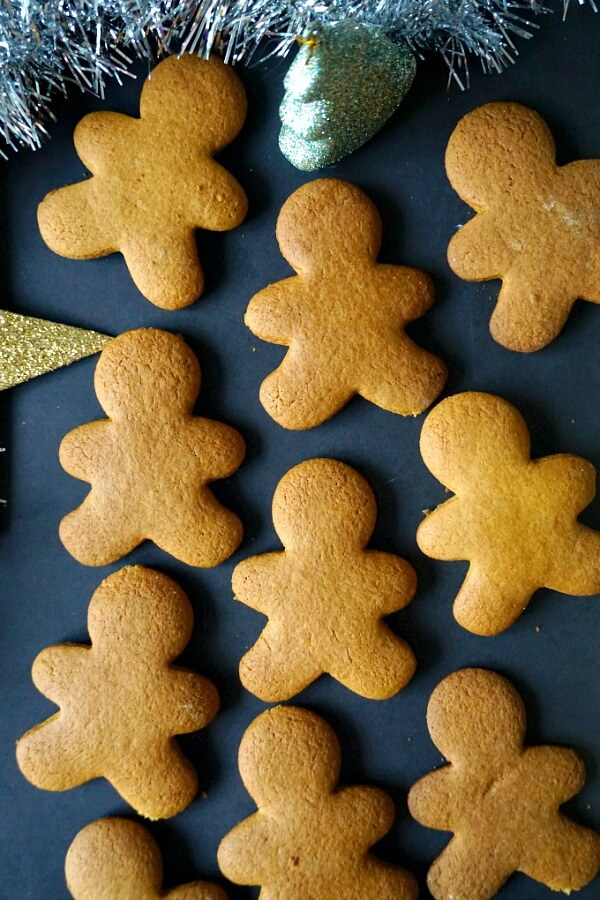 Overhead shot of 9 gingerbread man cookies on a black background