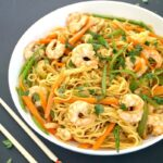 A white plate with shrimp stir fry and noodles and chop sticks on the side