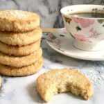 A stack of 5 coconut shortbread cookies, a cup of coffee and another half of a cookie