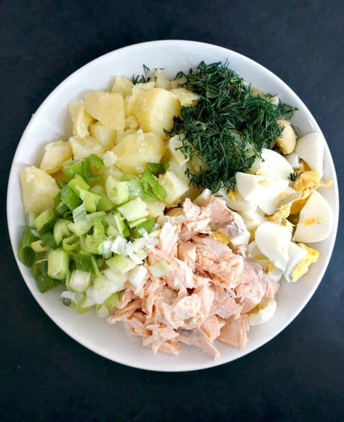 A white plate with chopped dill, spring onions, cubed potatoes, chopped eggs and flaked salmon