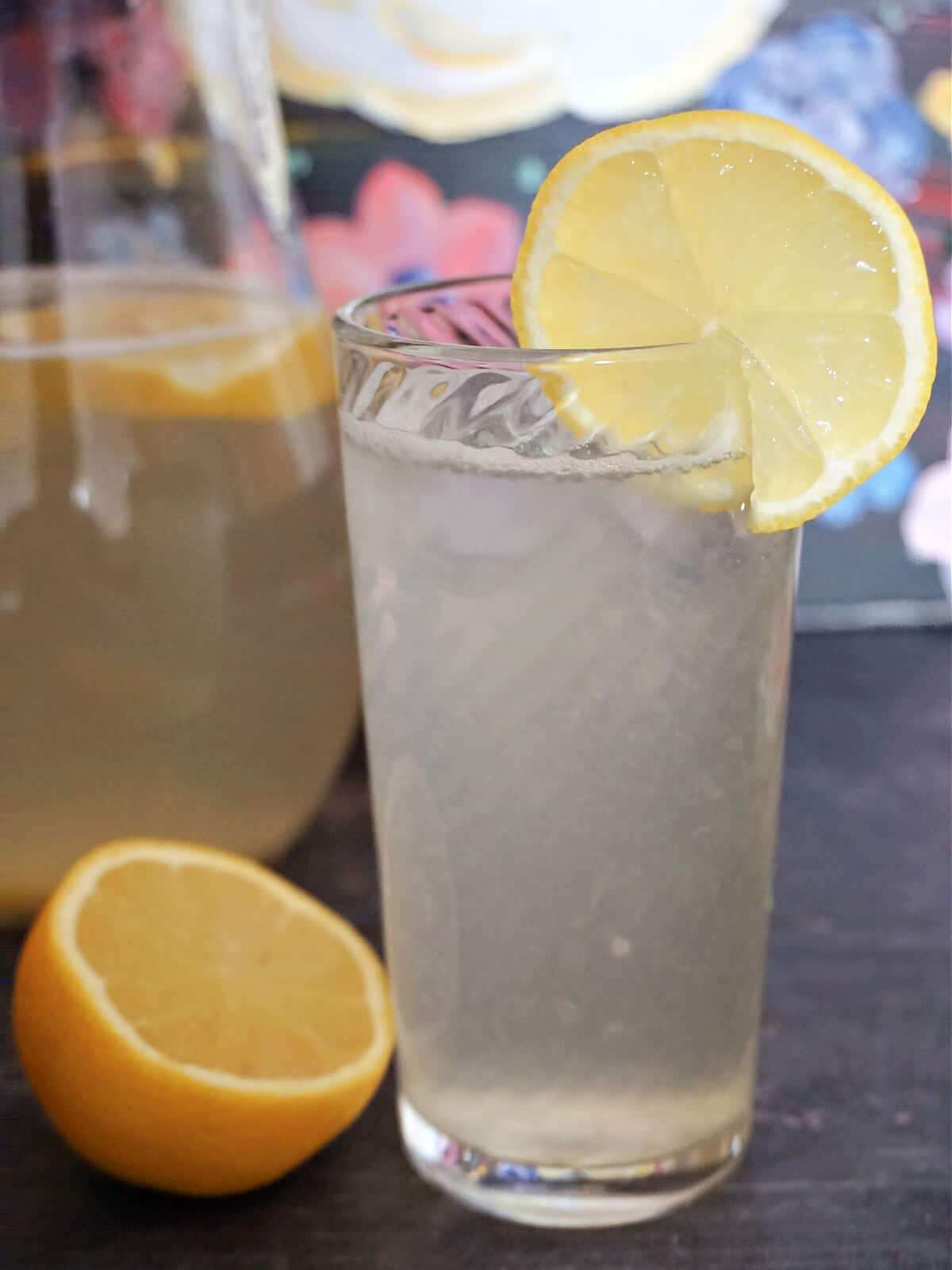 A tall glass with lemonade, a slice of lemon on the edge of it, and half a lemon next to the glass