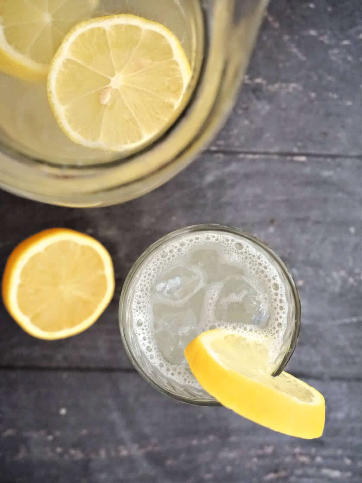 Overhead shot of a glass with lemonade and a slice of lemon on its edge, half a lemon next to the glass and a jug with more lemonade at the top