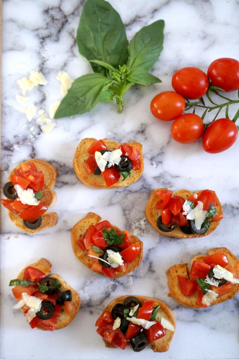 Overhead shot of a table with 7 tomato bruschetta, some basil leaves and cherry tomatoes