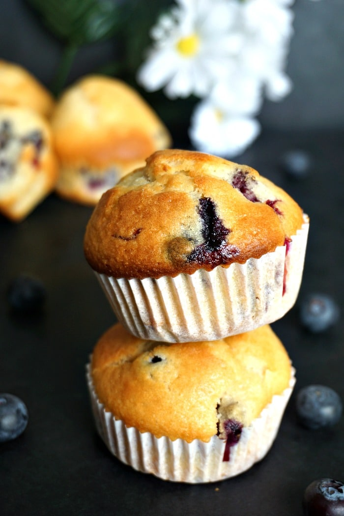 A stack of 2 blueberry muffins with blueberries around
