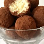A glass bowl with coconut balls dusted in cocoa powder