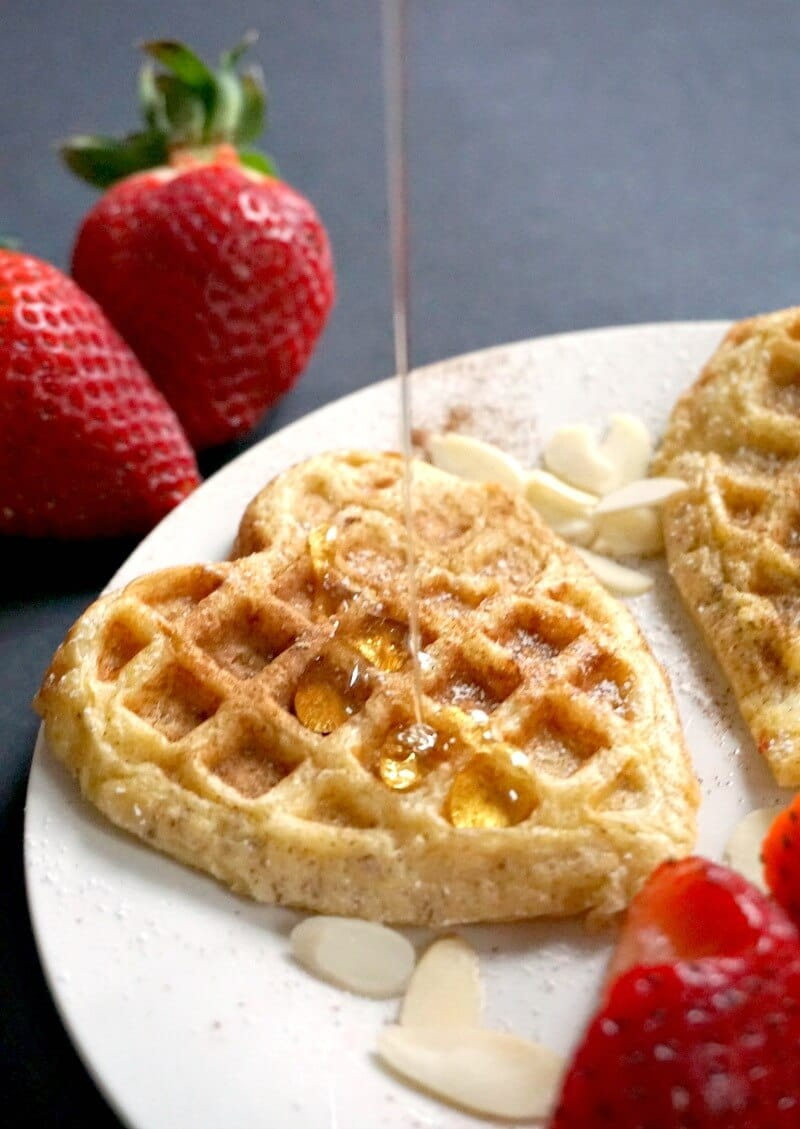 A white plate with maple syrup being drizzle on a french toast waffle