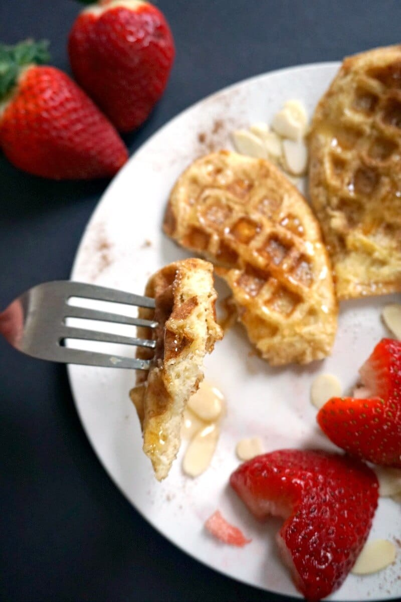 A white plate with french toast waffles and strawberries