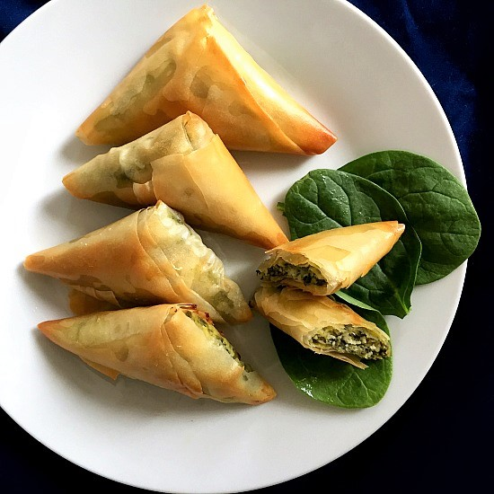 4 spanakopita triangles and one triangle halved on a white plate and 3 fresh spinach leaves