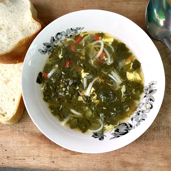 Overhead shot of spinach egg drop soup in a white bowl with 2 bread slices next to it