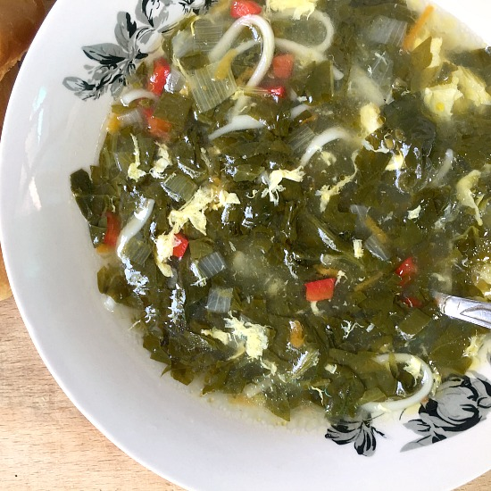 Close-up shot of a white bowl of spinach egg drop soup