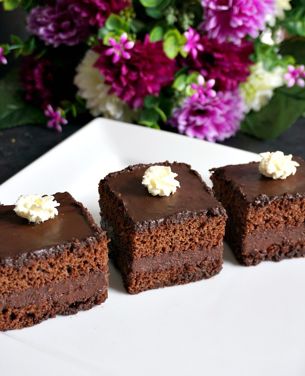 3 slices of chocolate cake with nutella filling on a white plate with purple flowers in the background