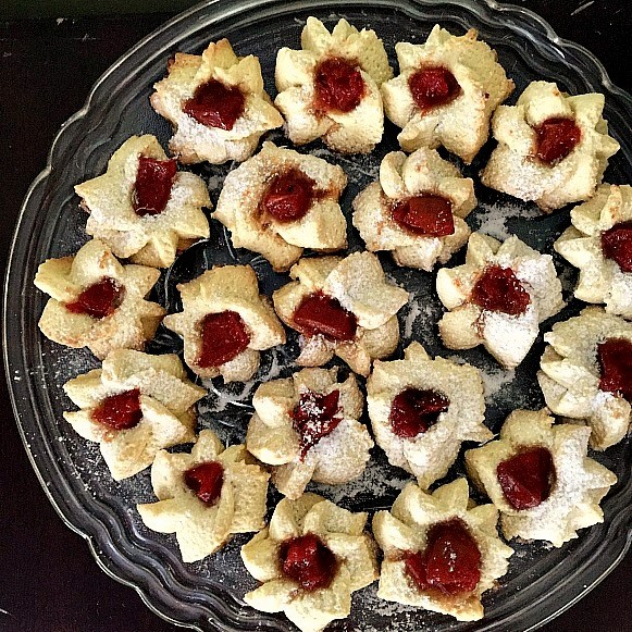 A glass plate with thumbprint shortbread cookies