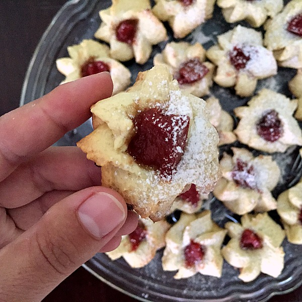 Close-up shoot of a thumbprint cookie with more cookies on a glass plate in the background
