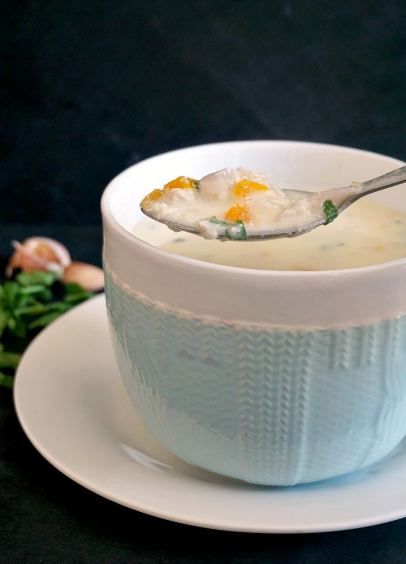A bowl of chicken soup with garlic and sour cream