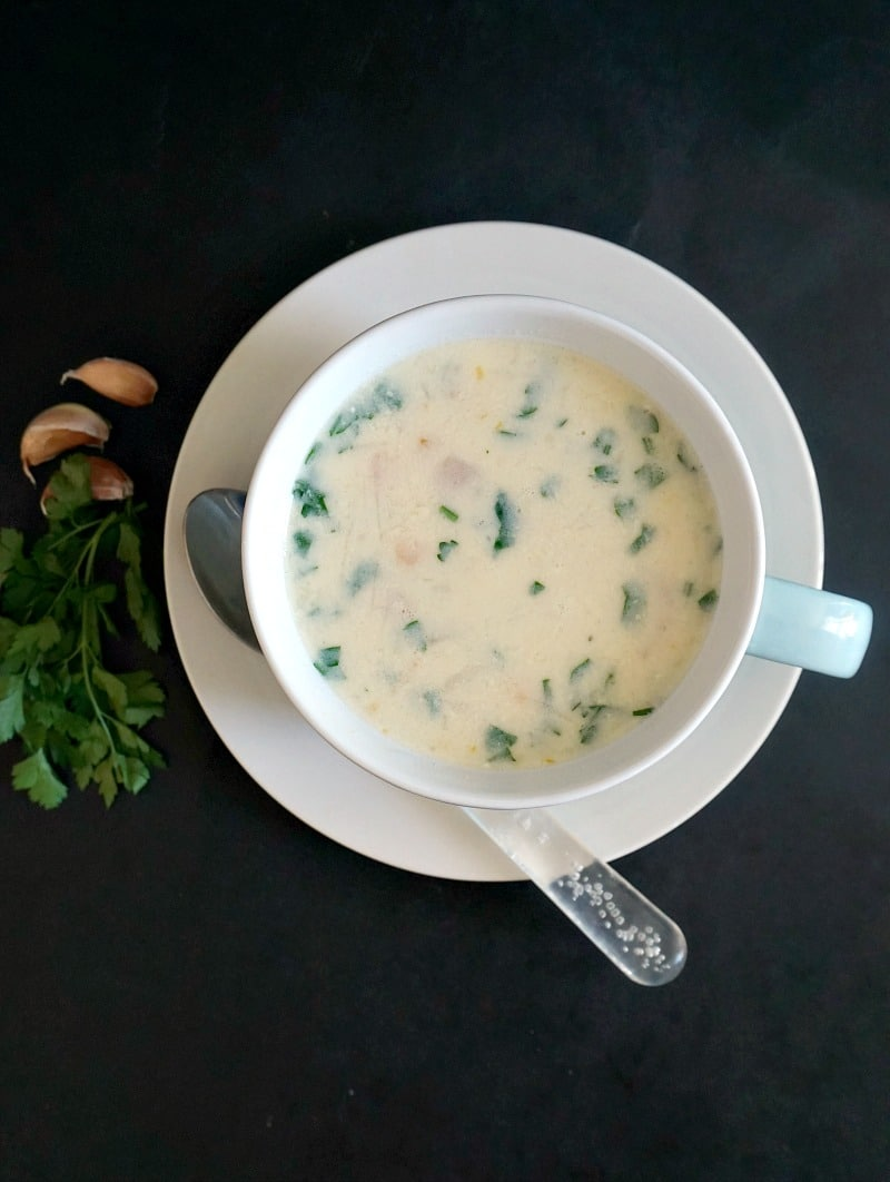 Overhead shoot of a white bowl of chicken soup with garlic and sour cream
