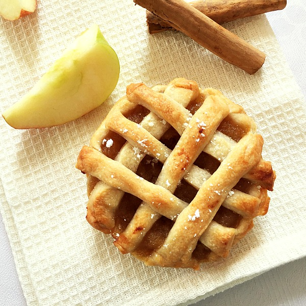 Overhead shoot of a mini apple pie with one apple wedge and 2 cinnamon sticks