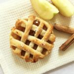 Overhead shoot of a mini apple pie with 2 apple wedges and 2 sticks of cinnamon