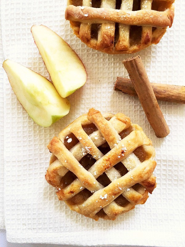 Overhead shoot of a mini apple pie with 2 cinnamon sticks and 2 apple wedges