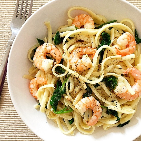 A white bowl of Pasta with Shrimps and Spinach with a fork next to it